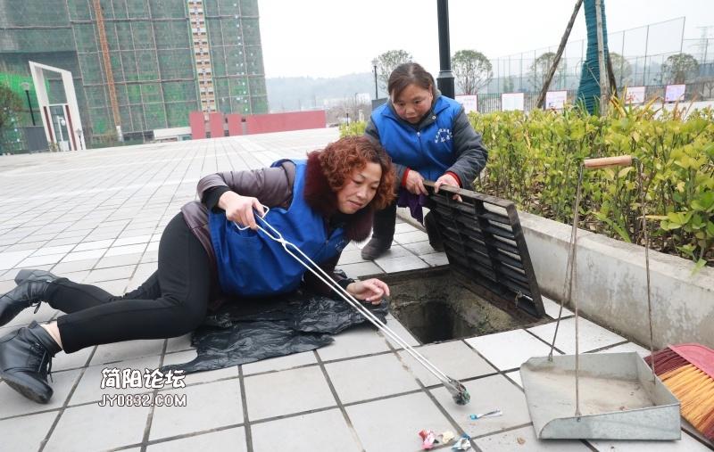 城北九义校的保洁阿姨正在清理地下水道的垃圾.jpg